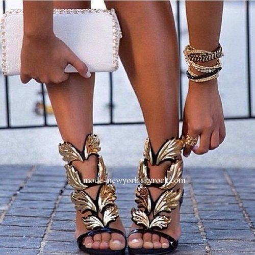 Des sandales haut perchées signées Giuseppe Zanotti Design en cuir verni noir ornées de volutes dorées façon Palme d'or  au prix de 1175 euros..