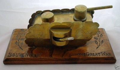 """Char briquet (20cm) en laiton avec petits canons en alu monté sur plaque en bois gravée """"Souvenir of the Great War"""". Sous la tourelle est caché le briquet. Le petit couvercle à l'arrière est un porte allumette. Sur le côté du char, gravure d'un soldat et d'une tête de cheval."""