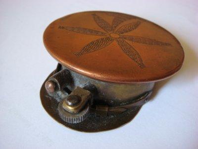 Briquet casquette en cuivre et laiton avec une fleur gravée sur le dessus