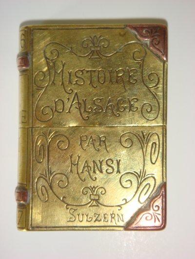 """Briquet de poilu reproduisant le Tome III du livre du dessinateur alsacien Jean Jacques Waltz, dit Hansi (1873-1951), gravé """"Histoire d'Alsace par Hansi  -  Sulzern"""""""