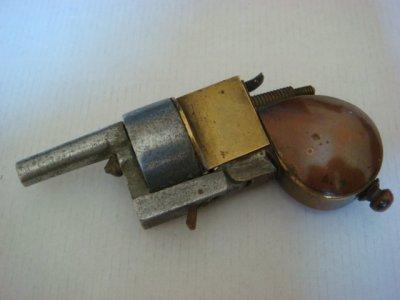 Superbe briquet pistolet en aluminium, cuivre et laiton. Les détails sont très bien réalisés, de la détente en cuivre aux balles dans le barillet (voir photo suivante). Le réservoir se trouve dans la crosse, le remplissage se réalisant en dévissant  la petite boule en dessous. Le briquet apparait en basculant le canon vers le bas.