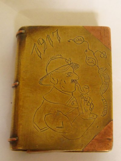 Briquet livre cuivre et laiton avec gravure d'un poilu fumant la pipe. Daté 1917.