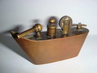 Briquet en forme de bateau de guerre, laiton et cuivre.