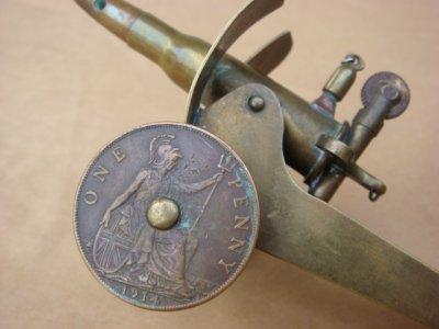 Détail du briquet canon: les roues sont des pièces anglaises de 1 penny datées 1914.