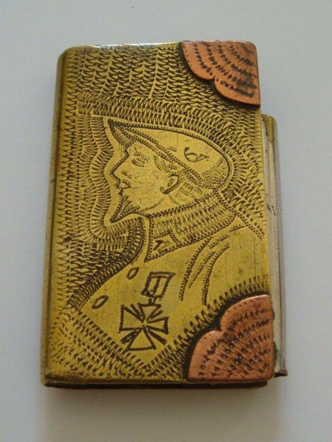 Briquet livre en laiton, coins en cuivre gravé d'un chasseur alpin du 12e BCA. Dim. 6,5x4 cm. Egalement briquet à amadou.
