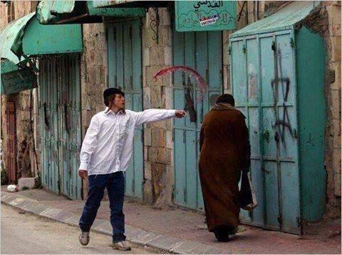 Qui est le # terroriste ... L'image montre un Juif vaporisant de l'alcool sur une femme palestinienne.