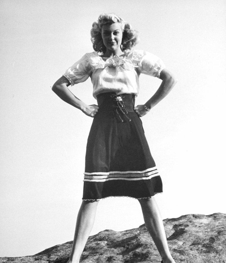 """Joan FULTON sous l'oeil de la photographe Martha HOLMES parodie une """"tea kettle"""" (bouilloire, théière) en Décembre 1946."""