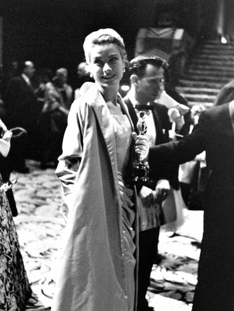 """Le 30 Mars 1955 a lieu la 27ème cérémonie des Academy-Awards à Hollywood au """"R.K.O. Pantages Theater"""" ; on comptera entre autres parmi les stars présentes (de haut en bas) Bing CROSBY et Kathryn GRANT / Grace KELLY qui recevra des mains de Marlon BRANDO un Oscar la récompensant pour son rôle dans le film """"The country girl"""" / Humphrey BOGART et sa femme Lauren BACALL / Marlon BRANDO ou encore Walt DISNEY. Les photos sont signées George SILK."""
