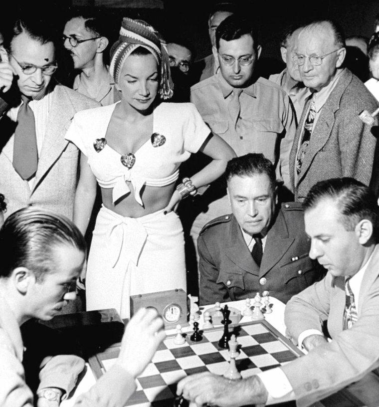 Août 1945, Walter SANDERS photographie des tournois d'échecs oû certaines stars s'adonnent au jeu ou participent simplement en tant que spectateurs, telles Barbara HALE et Bill WILLIAMS déguisés en Reine et en roi, Carmen MIRANDA donnant le coup d'envoi d'un tournoi, Linda DARNELL assistant à un tournoi, ou Jane NIGH jouant sur la plage de Santa-Monica beach aux échecs miniatures.