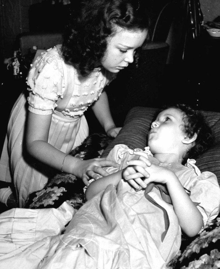 Gloria Jean en famille vue par Peter STACKPOLE en 1939, notamment avec sa petite soeur Bonnie (2 dernières photos) ou en compagnie de Joseph PASTERNAK et Deanna DURBIN. 1 photo également avec Hedda HOPPER.