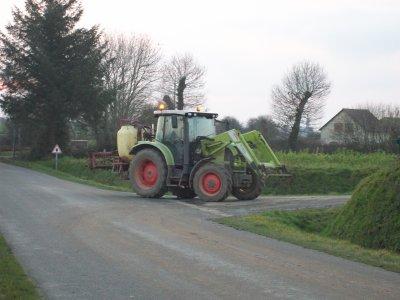 Tracteur Claas passant sur la route avec un pulvérisateur Hardi