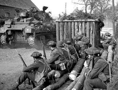 Des soldats britanniques regardent passer un tank Sherman, à Wertle, le 11 avril 1945