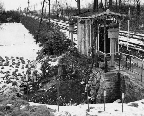 Prenant un abri partiel contre les fondations en pierre d'un bâtiment, avec mortier de 81 mm du Commandement de combat B, 23e Bataillon de chars, à Herrlisheim.