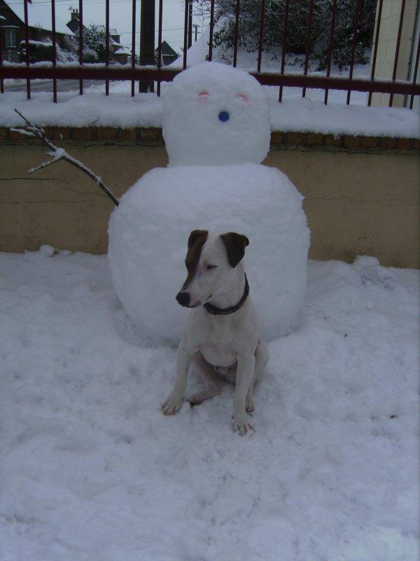 Petit pose devant le bonhomme de neige
