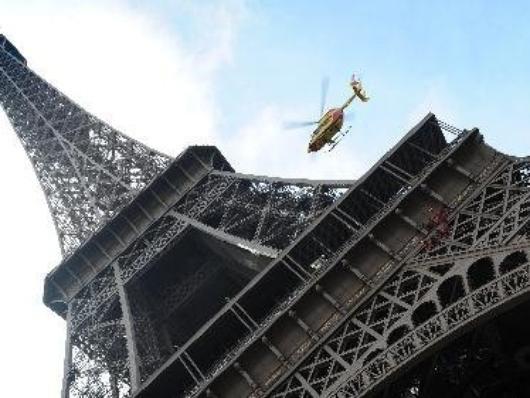 un helico de pompier atour de la tour Eiffel