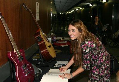 Vendredi 11 Février 2011 = Miley conduisant sa nouvelle voiture + signant des objets pour MusiCares aux répétitions des Grammy Awards.