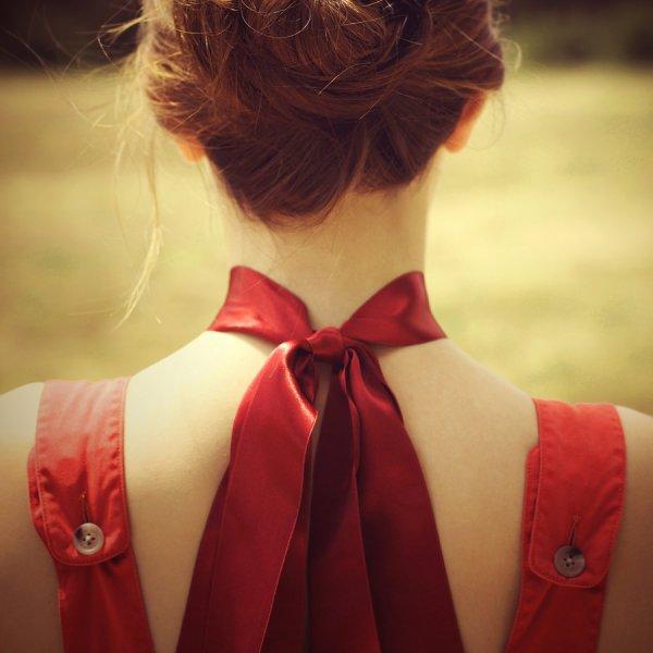 De très longs cheveux noués, Une rose y est accrochée, Une douce peau nacrée, D'un long ruban ornée
