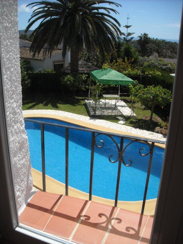 Vue de la piscine, de la Mer et de la verdure à partir de la terrasse et du salon