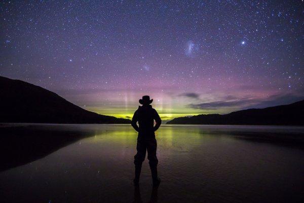 Un randonneur, dont la silhouette se découpe à contre-jour, contemplant une aurore polaire australe apparaissant à l'horizon de New Harbour Beach, dans le Southwest National Park en Tasmanie