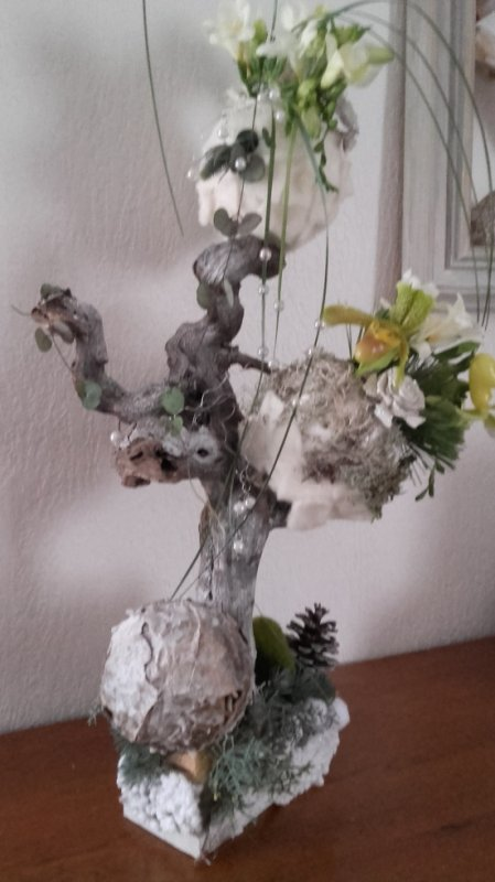 sur un cep de vigne des boules en polystyrène collage de feutrine ,lychen, sabots de venus dans pipettes