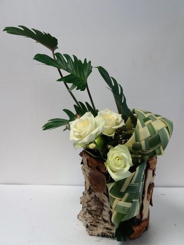 collage de copeaux de différents bois pour créer un contenant .travail de feuillages,3 boutons de roses pour agrémenter le tout..