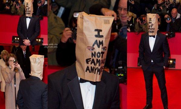 """Shia LaBeouf sur le tapis rouge du festival de Berlin à la premiere de son dernier film """"Nymphomaniac """"  avec, en complément de son smoking, un drôle d'accessoire sur la tête : un sac en papier portant l'inscription """"Je ne suis plus célèbre"""".  ( dimanche soir (9 Février ) à Berlin , Allemagne)"""