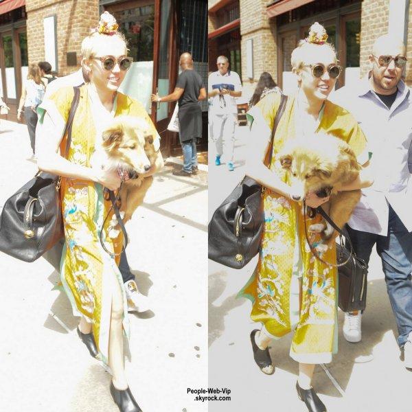 """C'est en quittant son hôtel new-yorkais que Miley Cyrus, vêtue d'un kimono jaune, a été aperçue avec son chiot """"Emu""""  (samedi après-midi (2 Août)."""