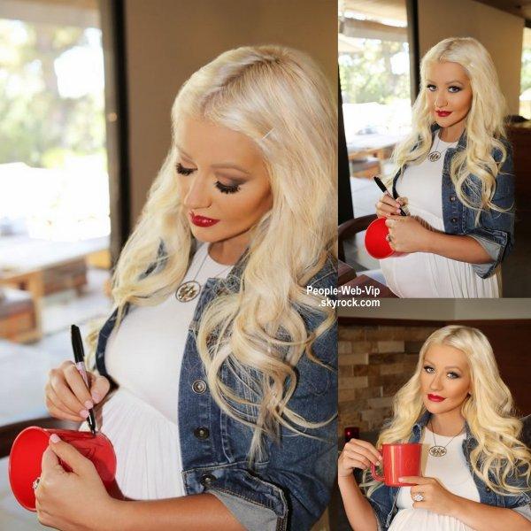 """Christina Aguilera a signé des tasses pour la charité et utilisé son ventre comme une table pour la campagne """"World Hunger Relief's """"Pass the Red Cup"""". ( mardi (5 Août)."""