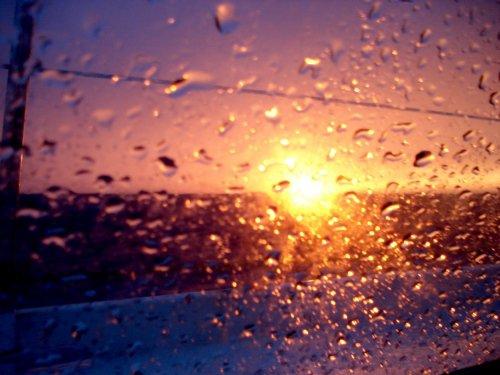 Une photo de lever de soleil a travers la vitre de la voiture