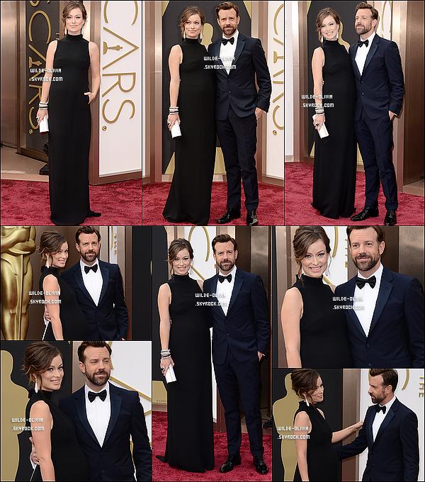 02/03/14 : Olivia et Jason Sudeikis étaient sur le tapis rouge de la cérémonie des Oscars 2014, à Los Angeles. Olivia portait une  robe  Valentino. Elle accompagnait Jason, qui est remettant cette année, et qui porte un costume  de Prada...