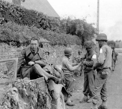 Près de Roncey la 2th Armored division avec un Kübelwagen de prise, un soldat allemand à bors, un GI4s tient une MP 40 à Notre Dame de Cenilly le 28 juillet.