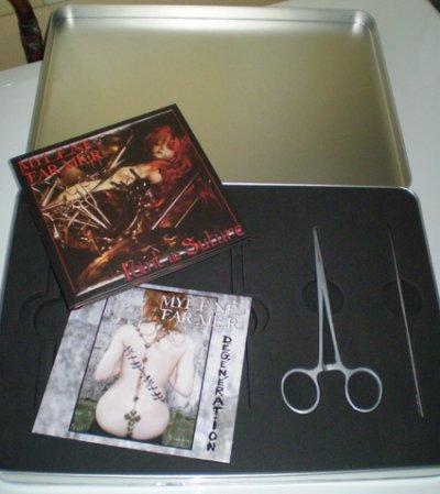 """Voici le collector de l'album """"Point de Suture"""" contenant une boîte métallique contenant l'album Point de Suture en version digisleeve (inclus le clip Dégénération), le CD promo Dégénération (qui est en fait différent du vrai promo du fait de la présence d'une référence différente) et un kit suture avec deux faux instuments chirurgicaux."""