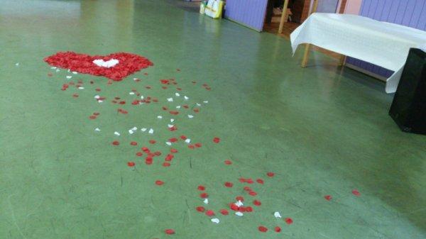 coeur en petales rouge et blanc avec trainees de petales jusque lentree de la salle