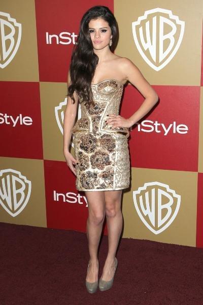 Selena est très sexy dans cette très jolie robe bustier dorée signée Atelier Versace