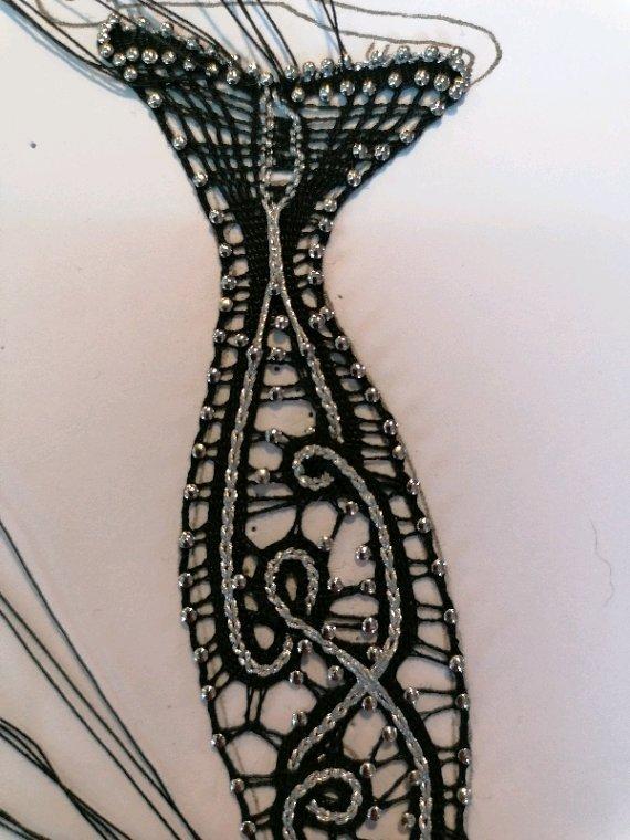 MONIQUE se lance un défi : une forme, démarrage avec tous les fuseaux en haut du motif, tout est travaillé en une seule fois. Très beau résultat. Remarquez le petit cintre qui tient la robe.