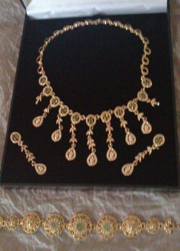 Parures Dorées A gauche: parure dorée avec pierres vertes comprennant   bracelets/ boucles d'oreilles/ collier A droite: Parure dorée avec pierres rouges comprennant: bague / boucles d'oreilles/ bracelet / collier