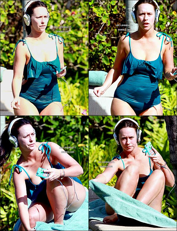 """.03/01/11 : Jennifer Love Hewitt, casque sur les oreilles, faisant """"bronzette"""" au bord d'une piscine à Hawaii.."""