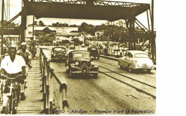 1931..pont  metallique  de  treichville..... - Cet ouvrage un peu primitif - un pont flottant -, édifié en 1931, occupait approximativement l'emplacement de l'actuel pont Houphouët Boigny. Franchissant la lagune Ebrié, il reliait le quartier du Plateau, au nord, au quartier de Treichville au sud. Il fut détruit en 1957, pour céder la place au nouveau pont. Celui-ci, construit en béton précontraint sur des pieux profonds, comporte 8 travées pour une portée totale de 372 mètres. A la fin des années 1960, un autre pont, nommé pont Charles De Gaule fut édifié selon les mêmes techniques, à quelques centaines de mètres à l'Est du pont Houphouët-Boigny, pour absorber une partie du trafic automobile en plein essor. Ce nouvel édifice, long de 592 mètres, est d'ailleurs dévolu à l'usage routier.