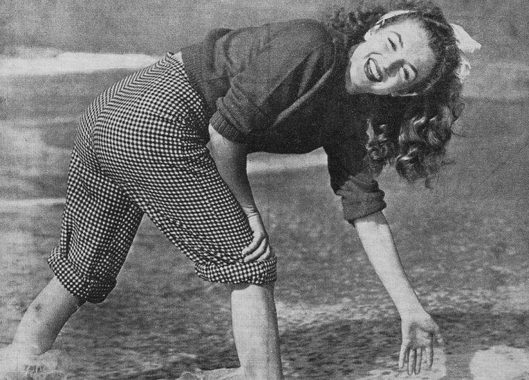 Session pull-over rouge et pantalon à carreaux sur une plage de Californie, by André De DIENES (1945).