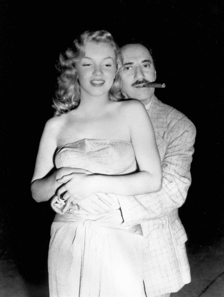 """1949 """"Love Happy"""" (La pêche au trésor). Backstages du film où Marilyn pose aux côtés de Groucho MARX ; Ce film est un pastiche de film policier avec les frères MARX. Groucho joue le détective Sam GRUNION lancé dans une histoire de diamants volés. (photos des MARX Brothers avec de gauche à droite, Chico, Groucho, Harpo et Zeppo MARX ; un 5ème frère fit partie de la """"troupe"""" et qui a disparu au fil du temps, Gummo)."""