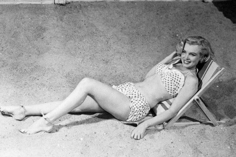 """1951, sur le tournage du film """"Love nest"""", Marilyn pose en bikini, bouteille de coca-cola à la main."""