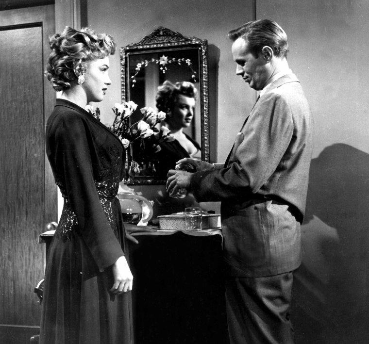 """1952, """"Don't bother to knock"""" (Troublez moi ce soir) de Roy BAKER / CRITIQUE / Alors qu'on aurait pu s'attendre à un rôle léger pour un premier rôle en haut de l'affiche, Marilyn endosse en effet les habits d'un personnage névrosé, fortement instable et donc potentiellement dangereux. Fasciné par les théories freudiennes, Hollywood a régulièrement porté son intérêt sur des cas cliniques, propices aux interprétations décalées et spectaculaires. Il faut avouer que, dans ce cas précis, la comédienne s'en sort plutôt bien et laisse déjà transparaître une aptitude à jouer les passionnées mélancoliques, les innocentes tourmentées, les femmes introverties mais anxieuses de faire exploser le carcan social et sexuel qui l'enserre. Marilyn portera ce type d'interprétation au firmament dans """"The Misfits"""" (1961). En attendant le film de HUSTON, Hollywood préférera la cantonner dans des personnages plus enjoués et gentillets, illuminant quelques films certes majeurs et enthousiasmants, mais avec pour effet de souvent sous-estimer son inclination à la tragédie. Marilyn en souffrira secrètement pendant sa trop courte vie, mais ceci est une autre histoire."""