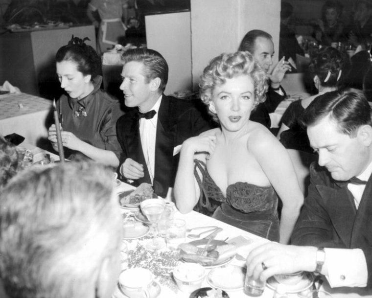 """8 Février 1952, Marilyn arrive dans une somptueuse robe moulante et très décolettée de couleure rouge à l'Hôtel """"Del-Mar"""" (photo) à Santa Monica. En effet, elle reçoit ce jour des mains de Lex BARKER et d'Arlene DAHL, le prix """"Henrietta Awards"""" de la """"Meilleure jeune personnalité du box-office 1951"""" / CRITIQUE / Pour cette soirée, Marilyn portait une robe au décolleté vertigineux - elle réajustait sans cesse sa robe sans bretelles - si bien que la presse s'en offusqua, un journaliste présent à la soirée, allant jusqu'à écrire que Miss MONROE était """"insignifiante et vulgaire dans cette robe"""" et que """"même dans un sac à patates, elle aurait été plus élégante"""". Marilyn  relèvera le défit, photos à suivre ! (part 2)."""