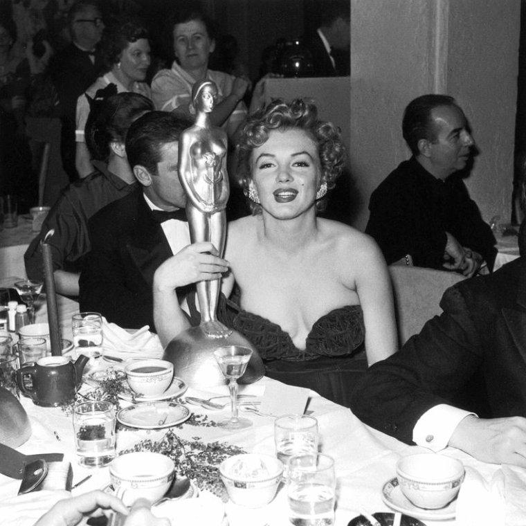 """8 Février 1952, Marilyn arrive dans une somptueuse robe moulante et très décolettée de couleure rouge à l'Hôtel """"Del-Mar"""" (photo) à Santa Monica. En effet, elle reçoit ce jour des mains de Lex BARKER et d'Arlene DAHL, le prix """"Henrietta Awards"""" de la """"Meilleure jeune personnalité du box-office 1951"""" / CRITIQUE / Pour cette soirée, Marilyn portait une robe au décolleté vertigineux - elle réajustait sans cesse sa robe sans bretelles - si bien que la presse s'en offusqua, un journaliste présent à la soirée, allant jusqu'à écrire que Miss MONROE était """"insignifiante et vulgaire dans cette robe"""" et que """"même dans un sac à patates, elle aurait été plus élégante"""". Marilyn  relèvera le défit, photos à suivre ! (part 4)."""