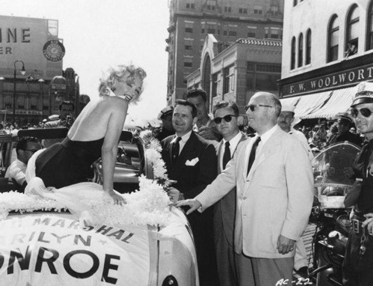 """1952 ATLANTIC-CITY : Il y a du monde en ce jour dans la ville pour l'élection de """"Miss America"""" ; les dirigeants de la FOX profitant de cette aubaine où toute la ville est de sortie pour un tel évènement, décident de faire parader Marilyn pour la promotion de son dernier film, """"Monkey business"""". Et c'est ainsi, qu'à bord d'une décapotable, Marilyn, les cheveux dans le vent se fait une joie de saluer les gens et de les remercier de mille baisers, les bras levés (part 2)."""
