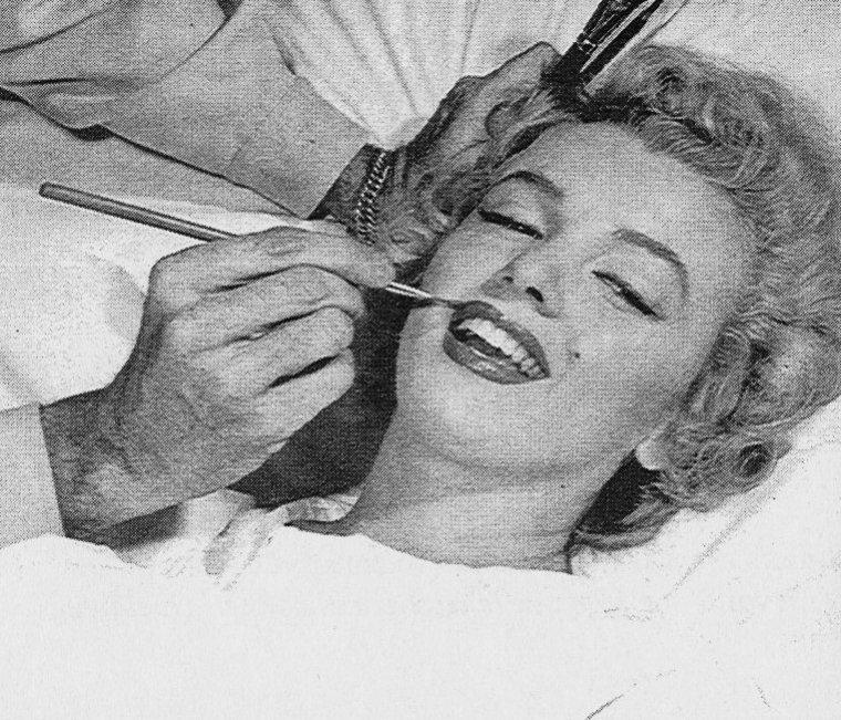 """En mai 1952 Marilyn est opérée de l'appendicite à Los Angeles. Pendant sa convalescence, elle reçoit un reporter photographe dans sa chambre d'hôpital, où on la découvre en train de lire une carte de Joe Di MAGGIO, qu'elle fréquente depuis quelques mois. A côté de son lit, se trouve un bouquet de roses envoyées par Joe. Marilyn avait eu des douleurs à l'appendice en mars de la même année, mais étant alors en plein tournage de """"Monkey Business"""", l'opération fut reportée en mai."""