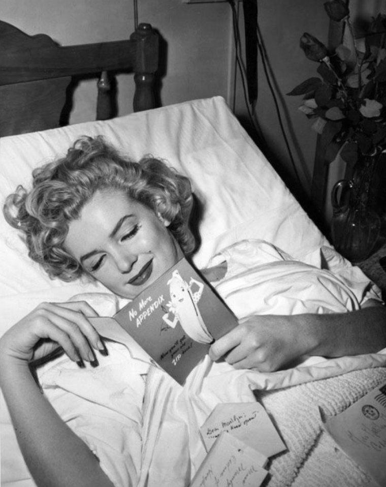 """En mai 1952 Marilyn est opérée de l'appendicite à Los Angeles. Pendant sa convalescence, elle reçoit un reporter photographe dans sa chambre d'hôpital, où on la découvre en train de lire une carte de Joe Di MAGGIO, qu'elle fréquente depuis quelques mois. A côté de son lit, se trouve un bouquet de roses envoyées par Joe. Marilyn avait eu des douleurs à l'appendice en mars de la même année, mais étant alors en plein tournage de """"Monkey Business"""", l'opération fut reportée en mai (part 2) / PETITE HISTOIRE / « Très important à lire avant l'opération. Cher Docteur, coupez le moins possible. Cela peut sembler futile je sais mais ce n'est pas de cela qu'il s'agit vraiment-le fait que je sois une femme est important et signifie beaucoup pour moi. Epargnez s'il vous plait (je ne saurais trop vous le demander) ce que vous pouvez-je suis dans vos mains. Vous avez des enfants et vous devez savoir ce que cela veut dire-je vous en prie Docteur-je pense je sais que vous comprendrez ! merci -merci- pour l'amour du ciel cher Docteur pas d'ablation d'ovaires-je vous en prie encore une fois de faire tout votre possible pour limiter les cicatrices - En vous remerciant de tout c½ur. Marilyn MONROE »."""