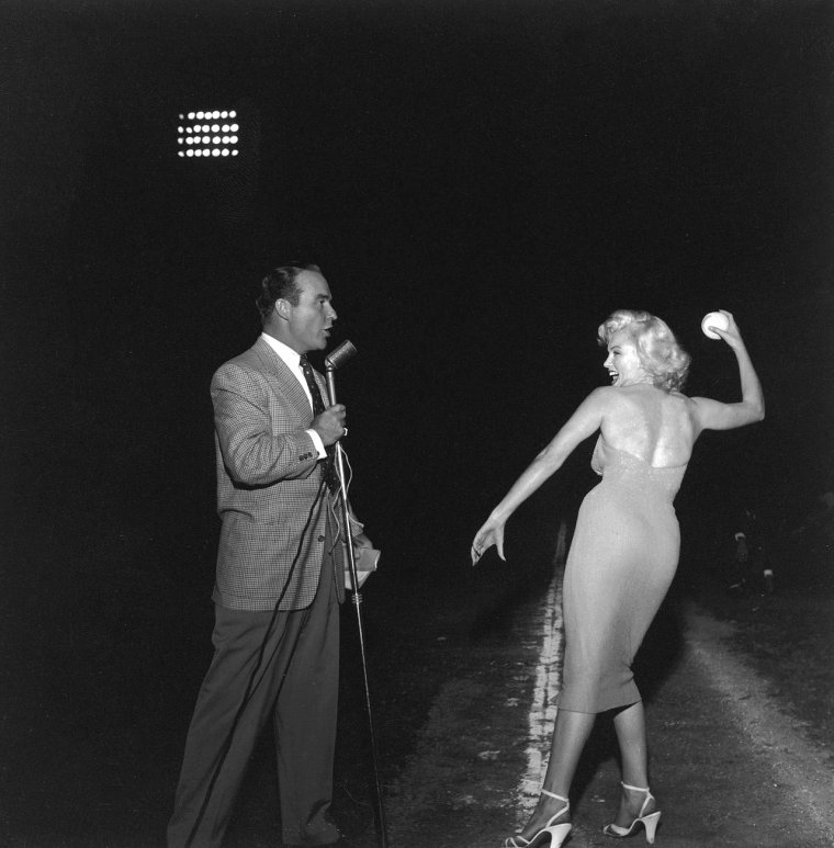 "Le 15 septembre 1952, Marilyn donne le coup d'envoi à un match de baseball à but caritatif, le sixième organisé annuellement: ""Out of this world series charity baseball game"", au stade ""Gilmore Field"" de Los Angeles. Parmi les participants: le boxeur Art ARAGON, et les acteurs Mickey ROONEY et Dale ROBERTSON (photo). Marilyn porte une autre robe rose avec laquelle elle fera la promotion du film ""Niagara"" (on y reviendra)."