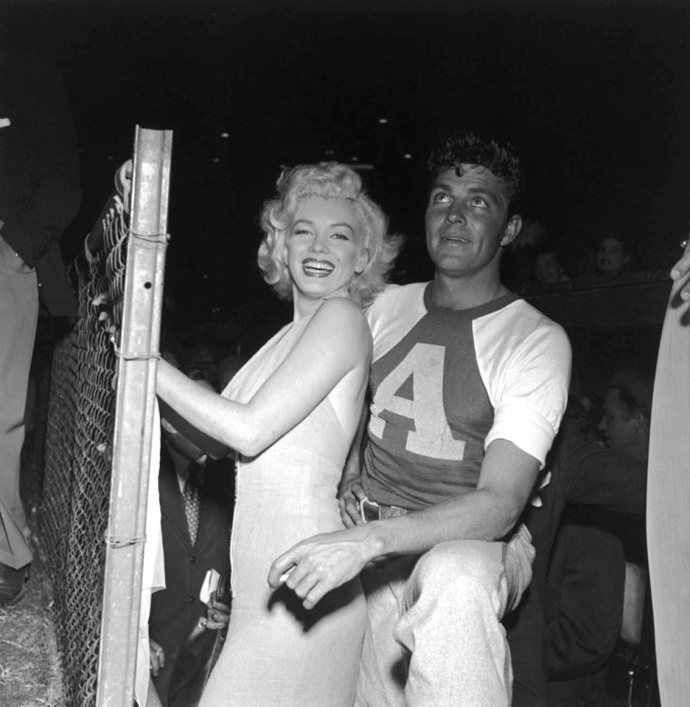 "Le 15 septembre 1952, Marilyn donne le coup d'envoi à un match de baseball à but caritatif, le sixième organisé annuellement: ""Out of this world series charity baseball game"", au stade ""Gilmore Field"" de Los Angeles. Parmi les participants: le boxeur Art ARAGON, et les acteurs Mickey ROONEY et Dale ROBERTSON (photo). Marilyn porte une autre robe rose avec laquelle elle fera la promotion du film ""Niagara"" (on y reviendra) (part 2)."