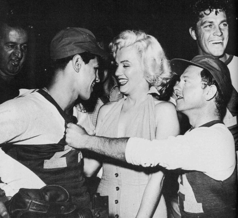 "Le 15 septembre 1952, Marilyn donne le coup d'envoi à un match de baseball à but caritatif, le sixième organisé annuellement: ""Out of this world series charity baseball game"", au stade ""Gilmore Field"" de Los Angeles. Parmi les participants: le boxeur Art ARAGON, et les acteurs Mickey ROONEY et Dale ROBERTSON (photo). Marilyn porte une autre robe rose avec laquelle elle fera la promotion du film ""Niagara"" (on y reviendra) (part 3)."